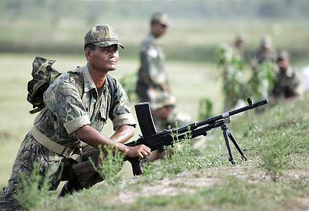 A paramilitary soldier mans his position before proceeding inside the villages of Lalgarh