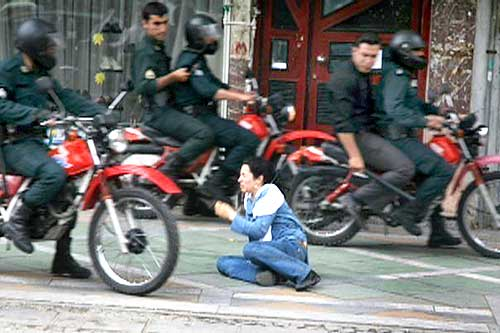 Security personnel look at a woman sitting on the ground as they ride past in Tehran