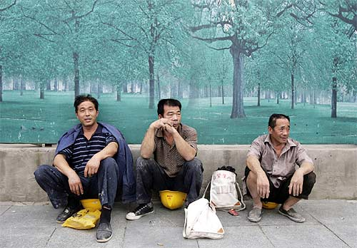 Chinese workers chat at a pavement in Beijing. Ordinary Chinese, polls say, consider India as their biggest enemy.