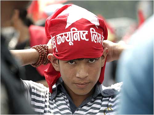 A boy puts on a 'Young Communist League' headband before taking part in an anti-government motorcycle rally in Kathmandu
