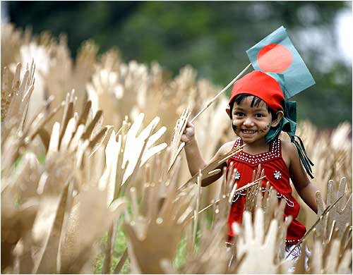 A child plays with the Bangladesh national flag