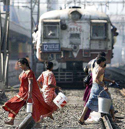 People cross a railway track as a suburban train is seen approaching in the background