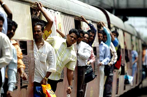 Commuters lean out of a train