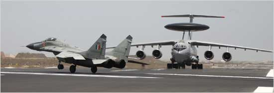 A MiG-29 lands after escorting the first IAF AWACS (background) at the Jamnagar air base