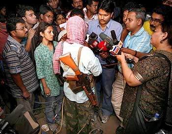 Maoist leader 'Kishenji', with back to camera, speaks to the media in Bholagara village, Bengal