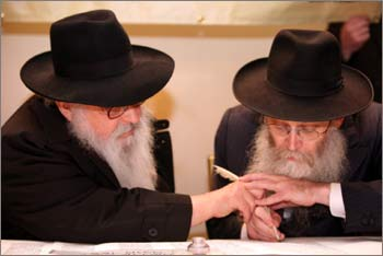 Rabbi Moshe Klein assists others in writing letters on a new Torah scroll that will replace the damaged one ruined by the terrorists at Nariman House.