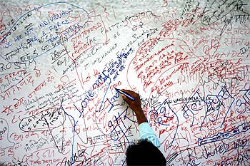 A visitor writes on a message board for the victims of 26/11 terror attack near the Taj Mahal Hotel.
