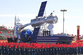 A float with a model featuring satellites is displayed during a  parade