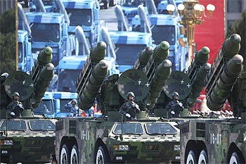 Soldiers stand in People's Liberation Army rocket launcher trucks they rumble past Tiananmen Square