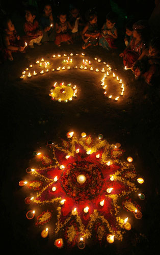 Children sit beside lighted lamps during Diwali celebrations in Siliguri
