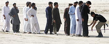 Men fleeing the offensive in South Waziristan being checked by police.