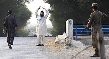 A cop approaches a man entering Dera Ismail Khan from South Waziristan by foot at a checkpost in Pakistan's South Waziristan
