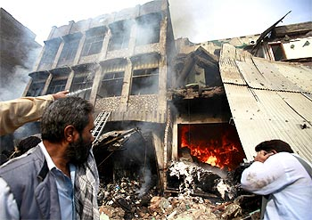 Locals look at a damaged building after a bomb explosion in Peshawar