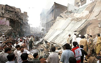 Residents, rescue workers and security officials at the blast site in Peshawar