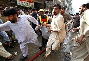 Rescuers carry the bodies of victims to ambulances at the blast site in Peshawar
