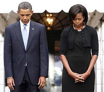US President Barack Obama and first lady Michelle Obama observe a moment of silence at the White House