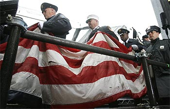 New York fire fighters carry a United States flag which survived the 9/11 attacks on the World Trade Center in New York