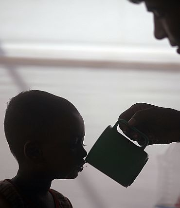 A father feeds his child Riayd, who is suffering from diarrhoea, with oral saline at the International Centre for Diarrhoeal Disease and Research in Dhaka