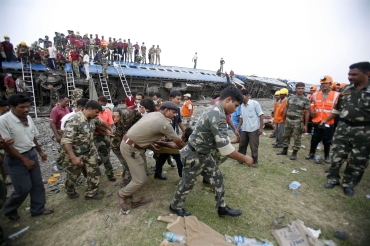 Soldiers carry the body of an injured victim at the site of a train mishap caused by Maoists in Bengal