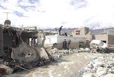 Victims retrieve their belongings from their partially damaged house in Leh