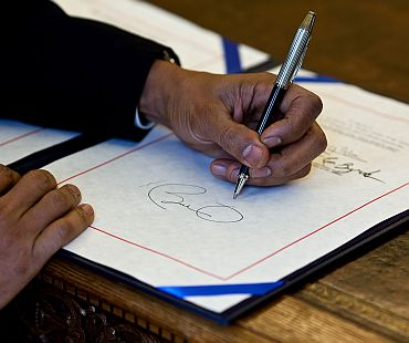 President Barack Obama signs a bill in the Oval Office