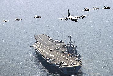 A US C-130 Hercules aircraft leads a formation of fighter jets over aircraft carrier USS George Washington in the East Sea of Korea in July, 2010