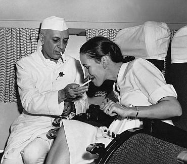 Nehru lights a cigarette for the then British high commissioner's wife