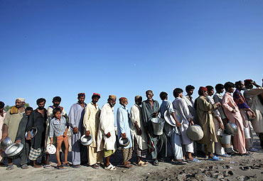 Flood-hit people queue up for food handouts in Sukkur, Pakistan