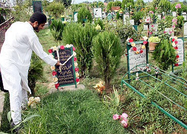 A youngster pays respect at Tufail's grave in the martyrs' graveyard, downtown Srinagar