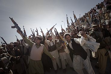 Members of the local Lashka hold their weapons while dancing in a show-of-force in Bajaur Agency