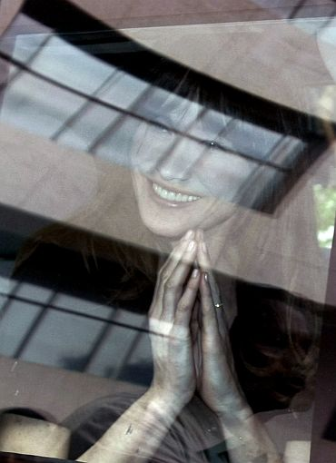 France's First Lady Carla Bruni-Sarkozy clasps her hands together in the traditional Indian welcome through the window of her car