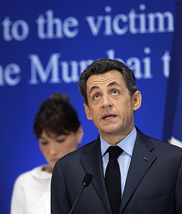 Sarkozy (R) delivers a speech as his wife Carla Bruni-Sarkozy stands by during a ceremony in tribute to the victims of the Mumbai terror attacks