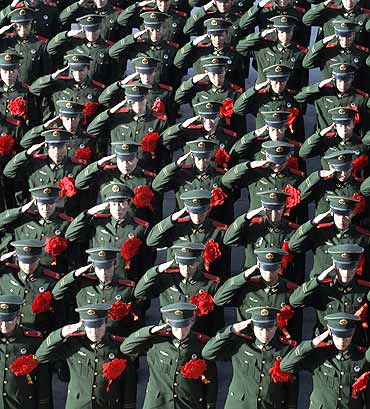 Paramilitary policemen salute during a ceremony at an army base in Taiyuan, Shaxi province