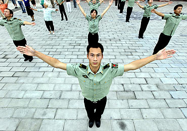 Staff members of the PLA take part in a gymnastic exercise session in Taimiao, Beijing
