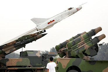 A boy looks at old PLA missile launchers on display at the China Aviation Museum