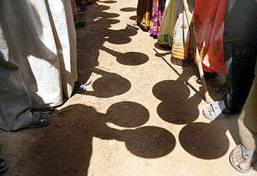 Villagers hold empty plates as they stand in front of a government office to protest against corruption