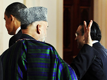 Afghanistan President Hamid Karzai (C) waves as he and Pakistan's President Asif Ali Zardari (R) depart with US President Barack Obama (L) after addrerssing a joint conference at the White House