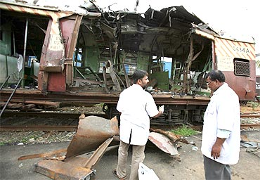 Forensic officers examine a damaged train compartment hit by bomb blast in Mumbai on July 12, 2006