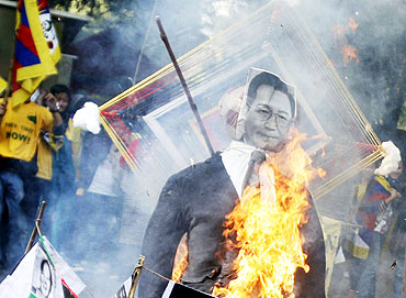 Tibetan exiles burn an effigy of Chinese Premier Wen Jiabao during a protest against his visit to In
