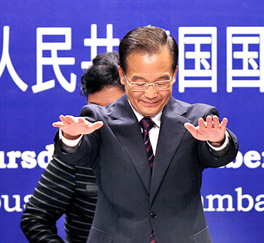 Chinese Premier Wen Jiabao gestures before taking his seat at an event