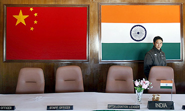 A man walks into a conference room used for meetings between military commanders of China and India