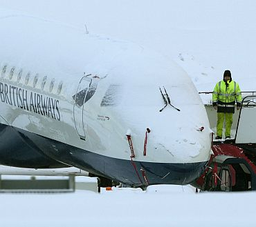 An engineer stands next to a snow covered British Airways aeroplane at Edinburgh Airport, in Edinburgh, Scotland