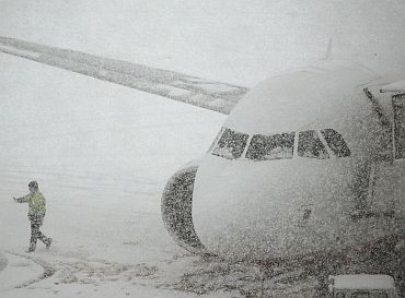 A worker walks past a plane parked on the snow covered tarmac of Zurich airport