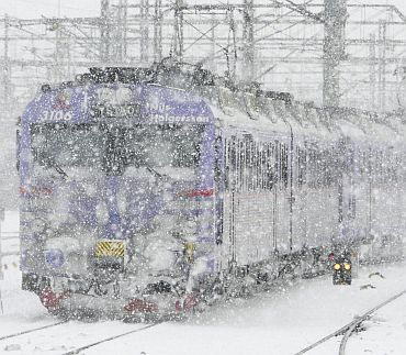 A commuter train travels into Malmo central railway station during heavy snow