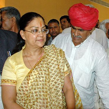 Former Rajasthan CM Vasundhara Raje and Gujjar leader Kirori Bainsla walk back after news conference in Jaipur