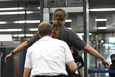 A passenger is checked by security personnel at the main terminal of Frankfurt's airport