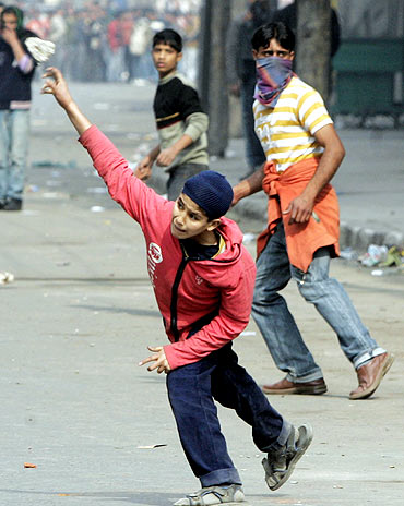 A Kashmiri protester throws a stone towards a policeman during a protest in Srinagar