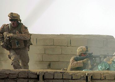 A US Marine from Bravo Company of the 1st Battalion, 6th Marines runs during a heavy gun battle in the town of Marjah, in Nad Ali district of Helmand province