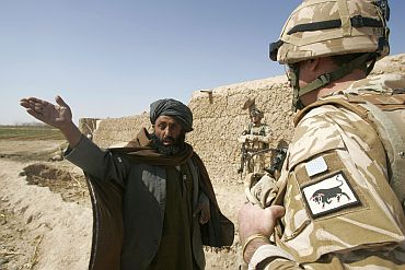 Colonel Matt Beazeley of the 28th Royal Engineer Regiment talks to a local Afghan farmer