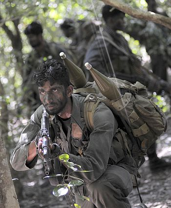 A Sri Lankan soldier keeps watch during a patrol in the jungle in the Puthukkudiyirippu area